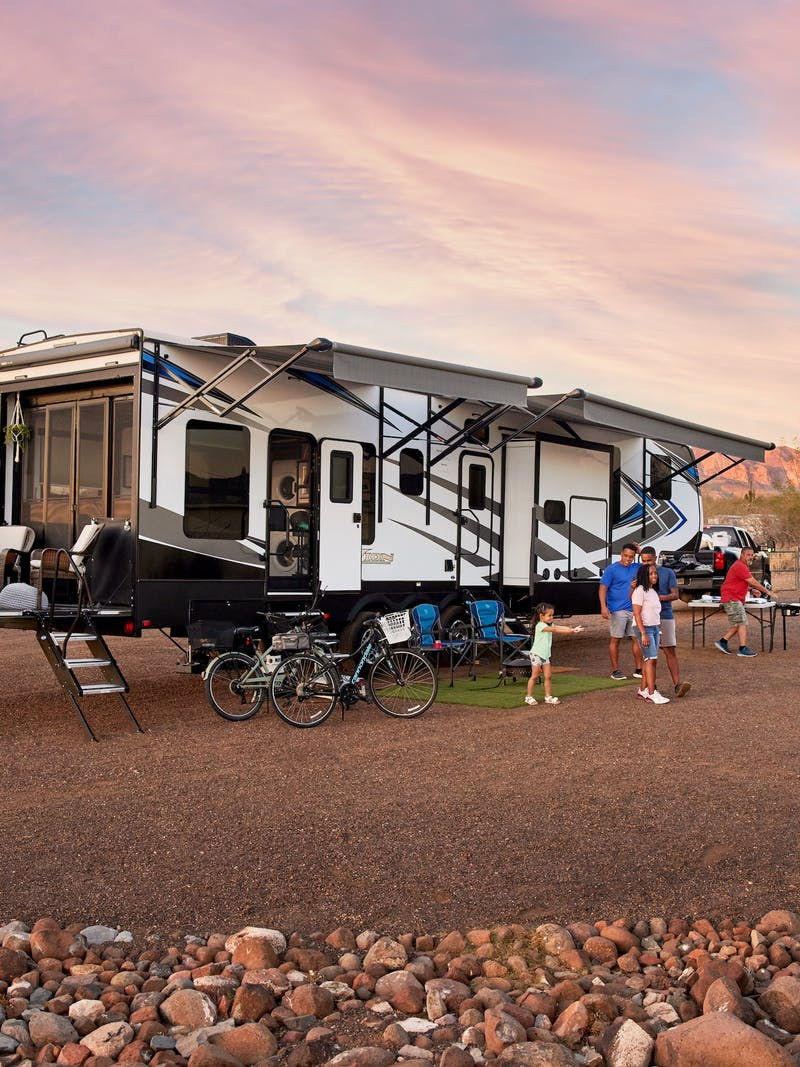 Robin, Warren and their family play outside of their Keystone Fuzion toy hauler RV.