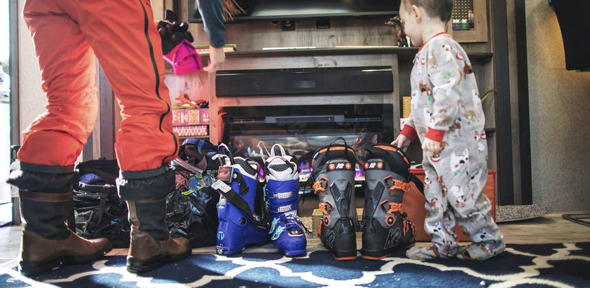 Ski boots are lined up by the fireplace inside an RV as a woman prepares to gear up for skiing.