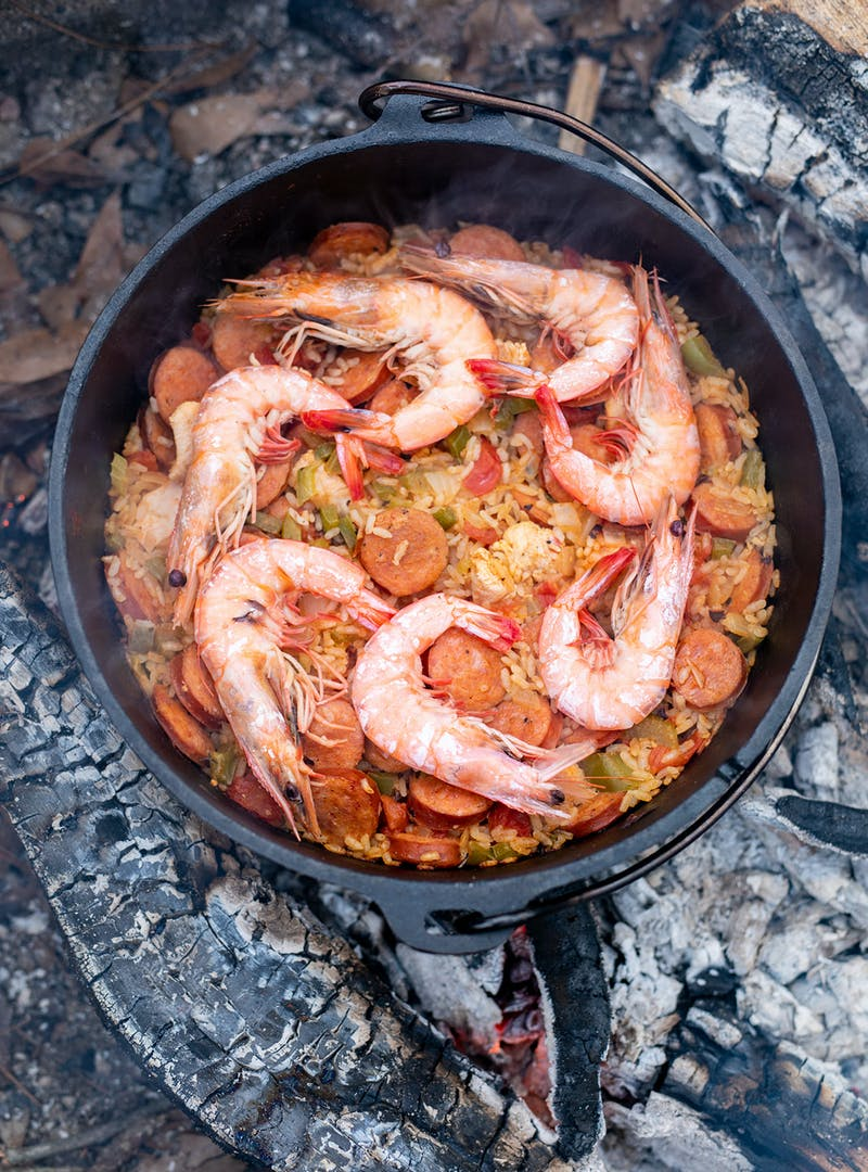 Adding shrimp to the jambalaya to cook.