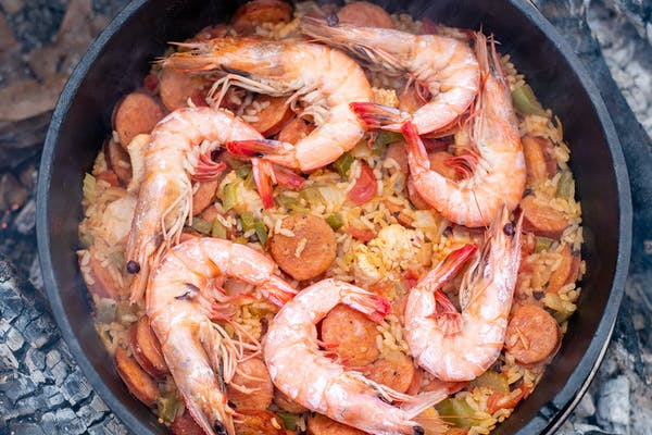 Cooked shrimp lined up on top of finished Jambalaya.
