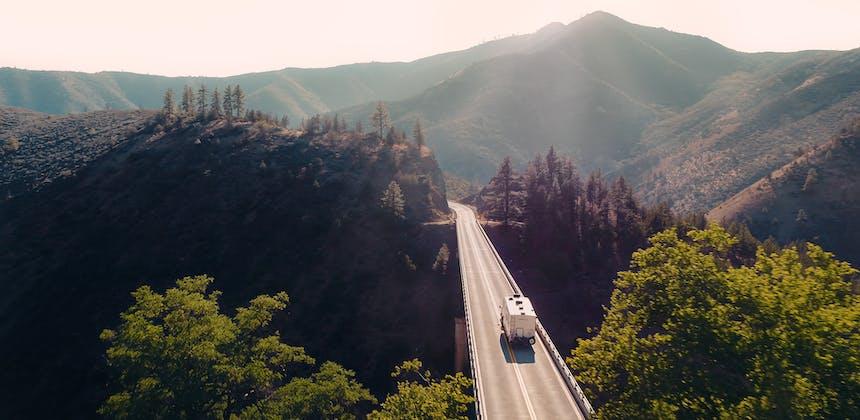 A fifth wheel RV driving down a bridge through mountains.