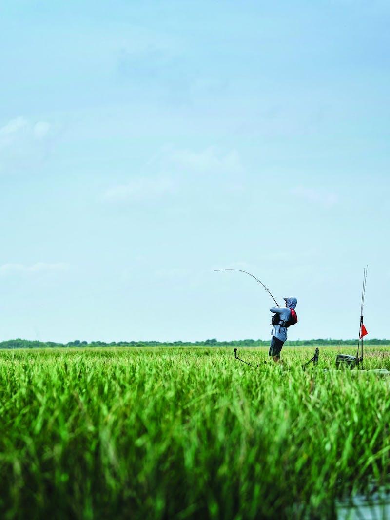 Kayak fisherman reels in fish standing among river grass