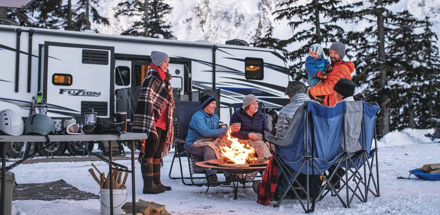 A family sits around a campfire outside of their RV, surrounded by snow.