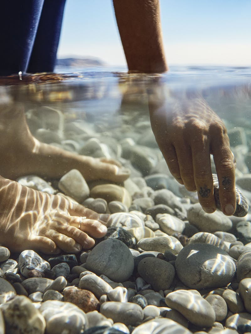 A woman picks up a rock from a shallow lake.