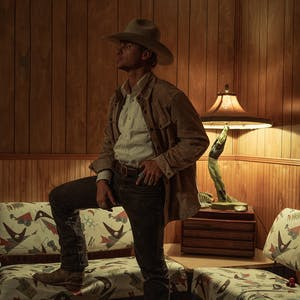 Man in a cowboy hats standing in wood paneled room, looking away from the camera, with leg up on a couch