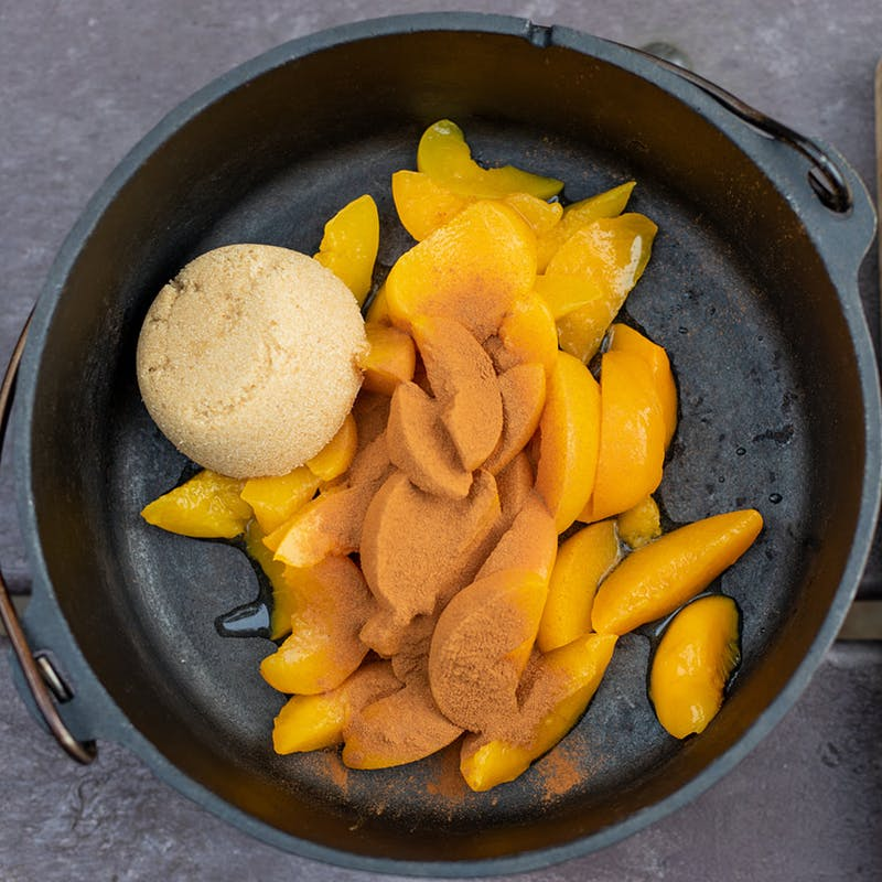 Peaches in a dutch oven with brown sugar and cinnamon.
