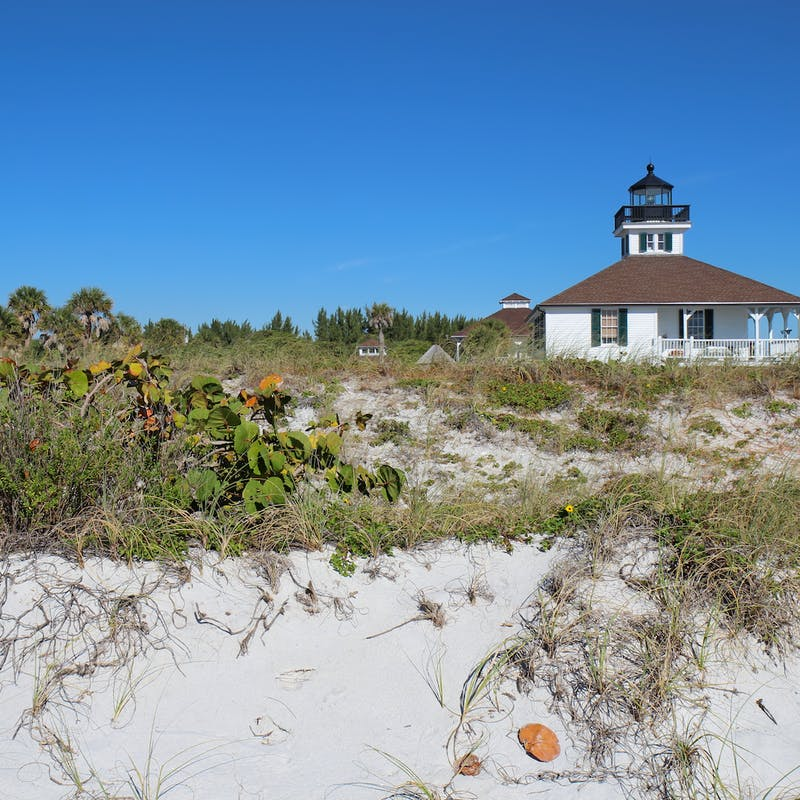 The Port Boca Grande Lighthouse on Gasparilla Island, Florida viewed from the sand dunes with sea oats and sea grape in the foreground and a clear blue sky
