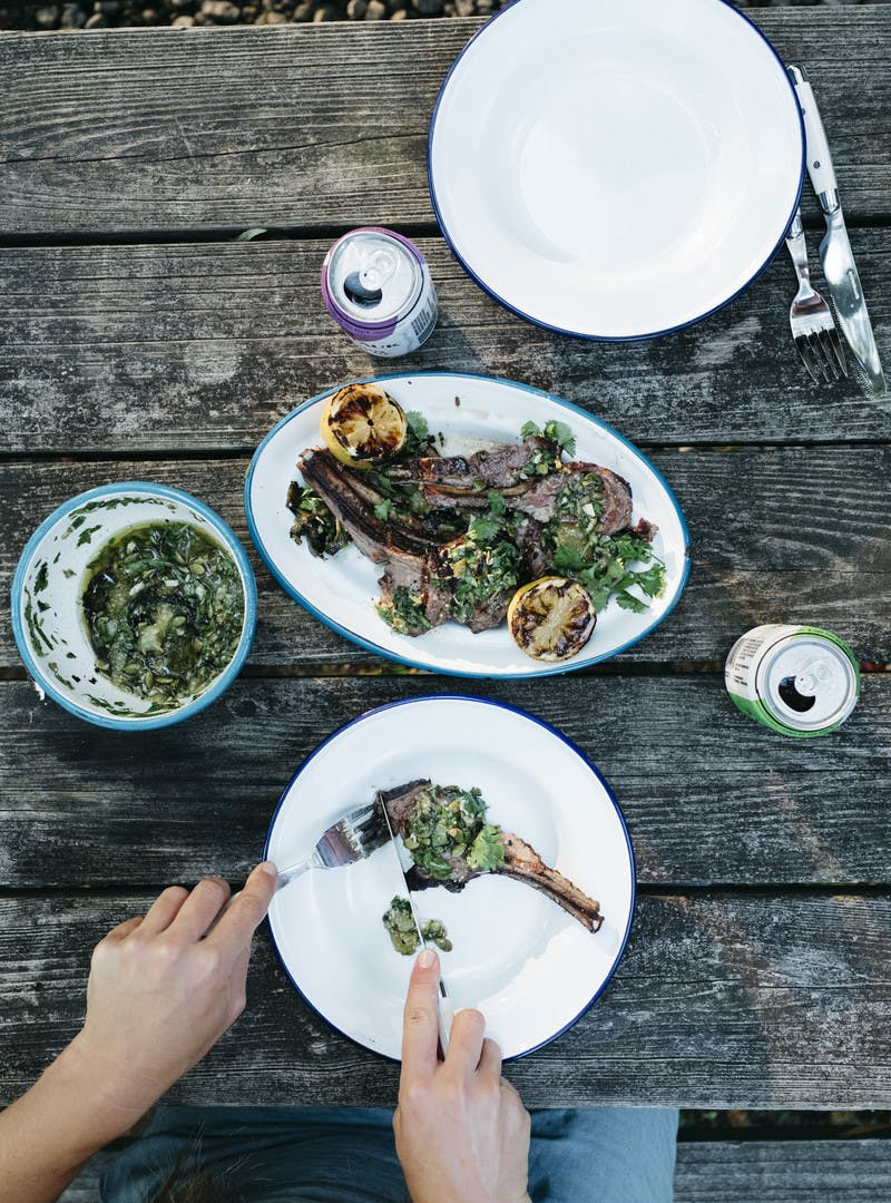 A serving of lamb plated and being cut into by two hands holding a fork and knife.
