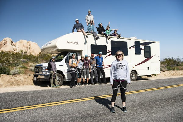 Participants from First Descents gather around a Jayco Class C RV in Joshua Tree National Park.