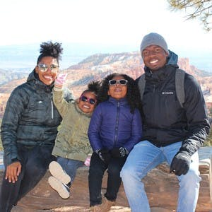 An African American family of 4 wearing winter jackets sits on a rock and smiles for the camera while wearing sunglasses.