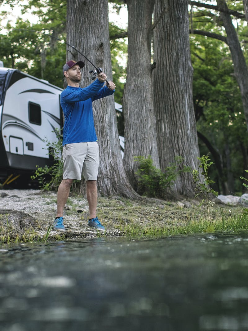 Robert Field fishes in a lake with his Keystone Cougar parked behind him.