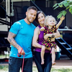 A portrait of Lauren and Fraser Bayley with their daughter and one of their dogs.