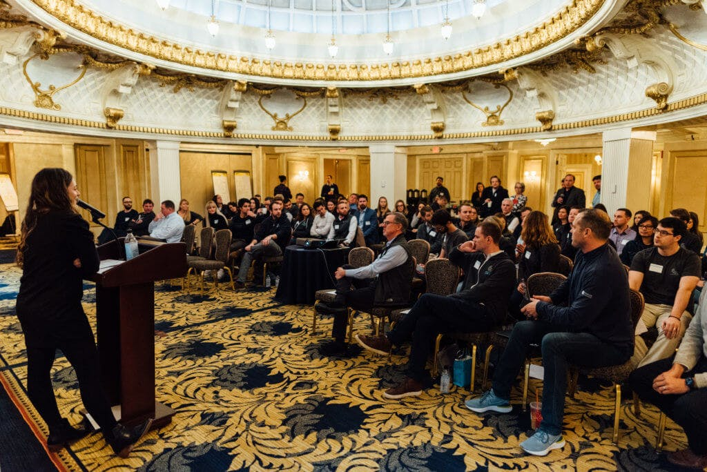 A person presenting in-front of a large room full of people sitting