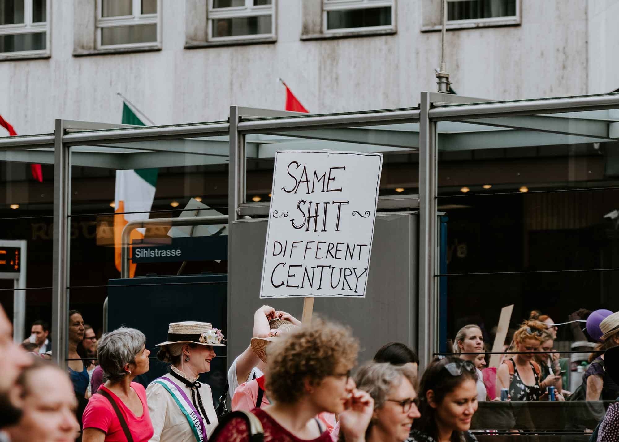 """Protester reading a sign that says """"same shit different century"""""""