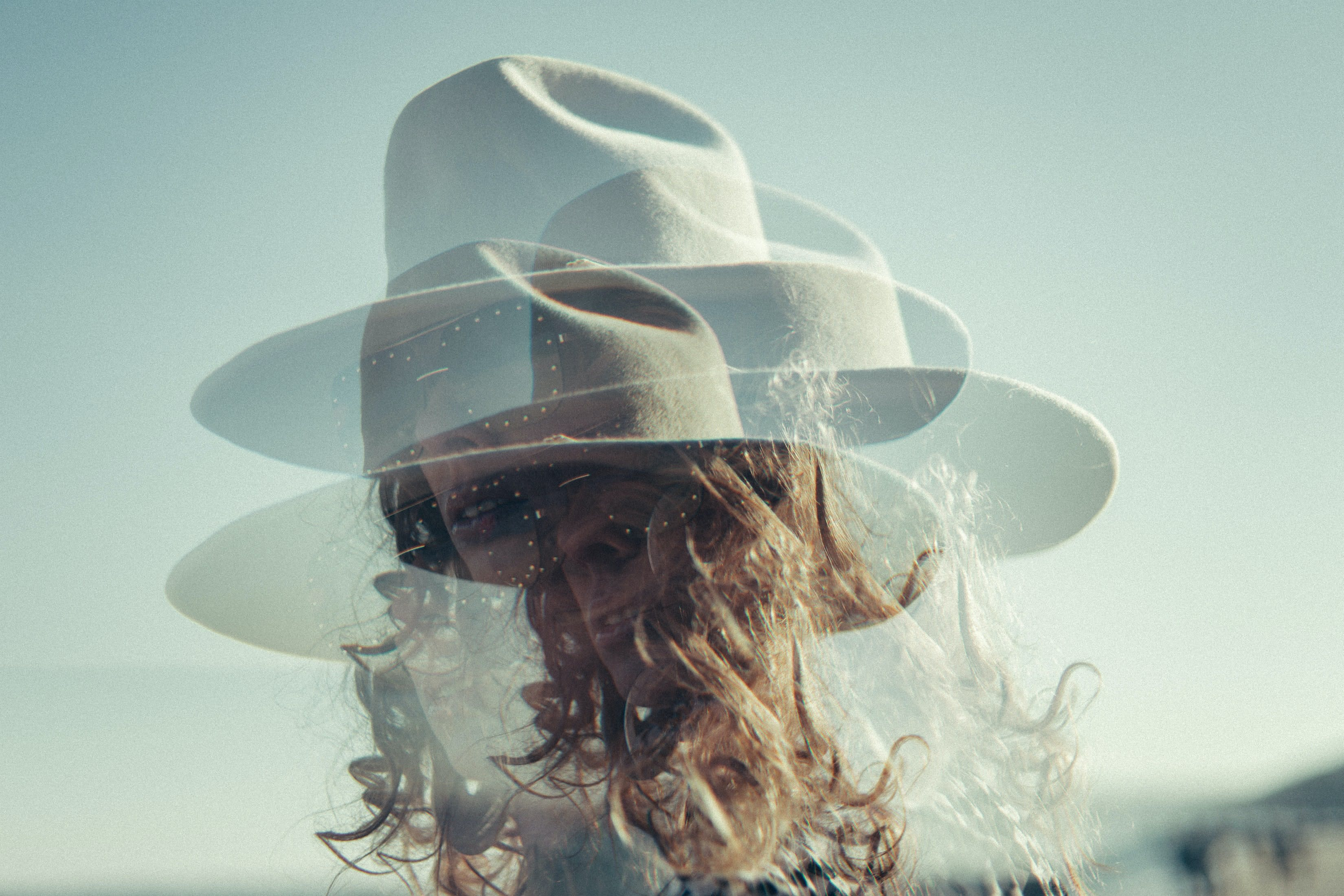 doubled image of woman in wide brim hat