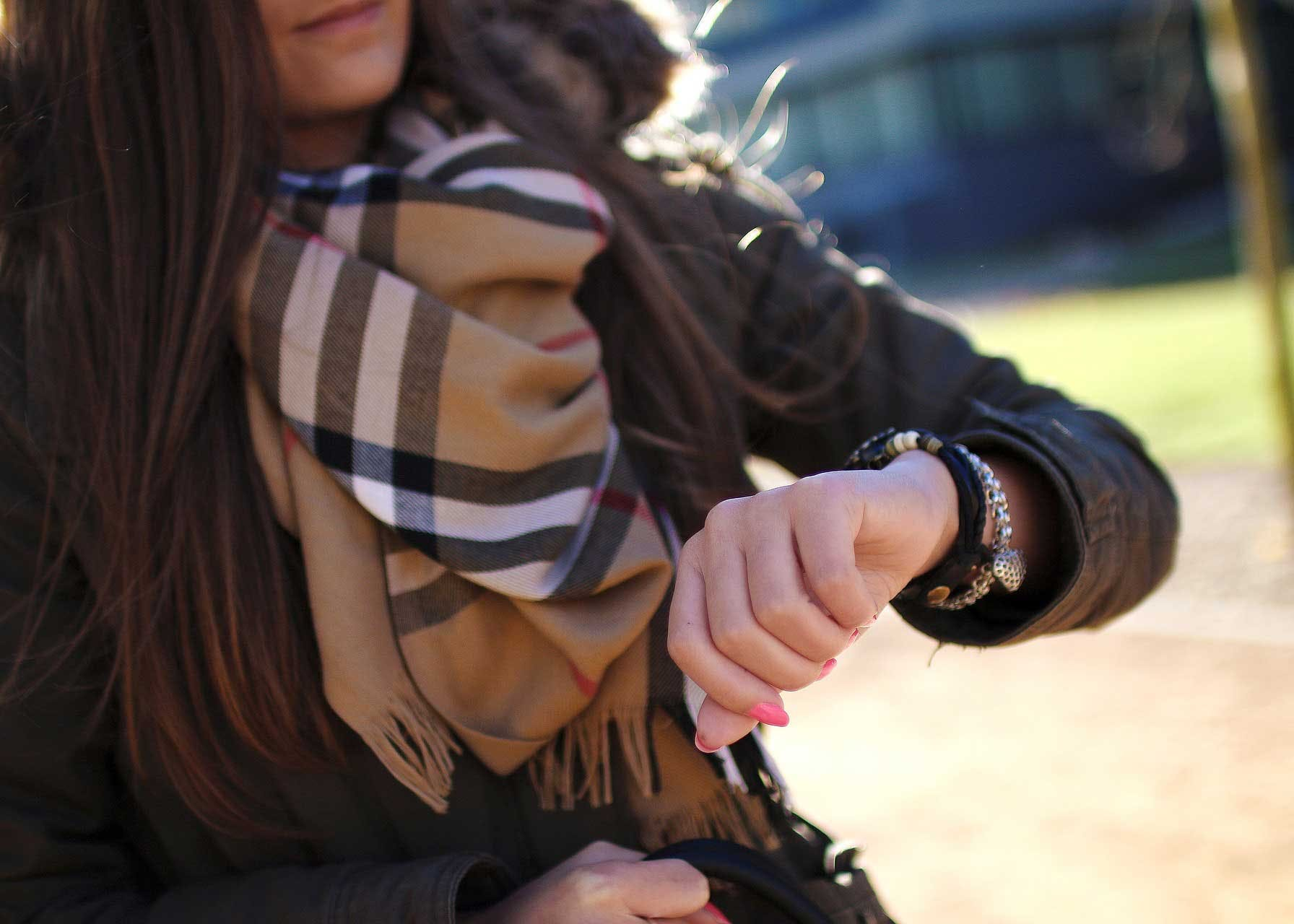 Woman wearing a Burberry scarf and checking her watch