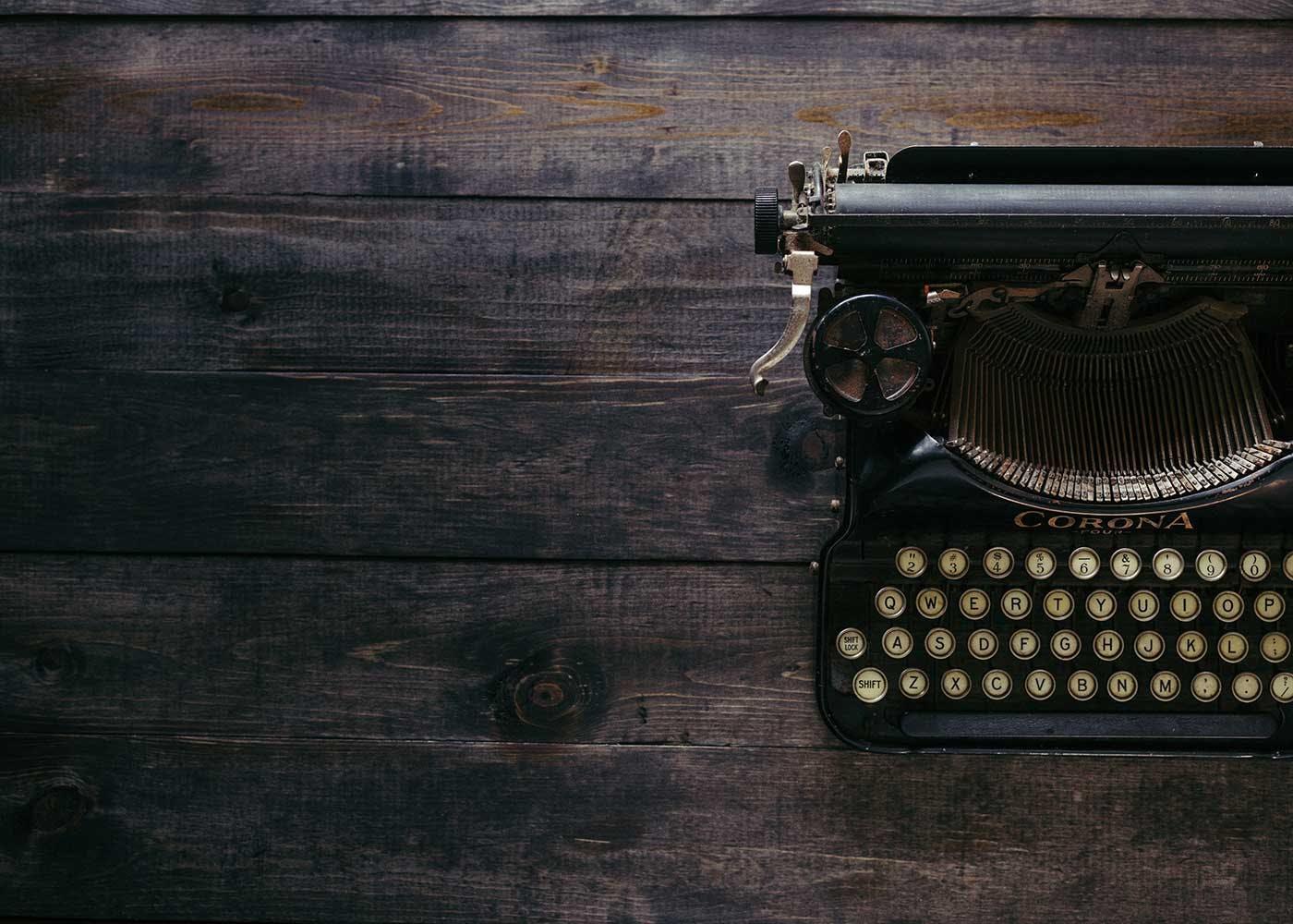 Old black typewriter on a wooden desk