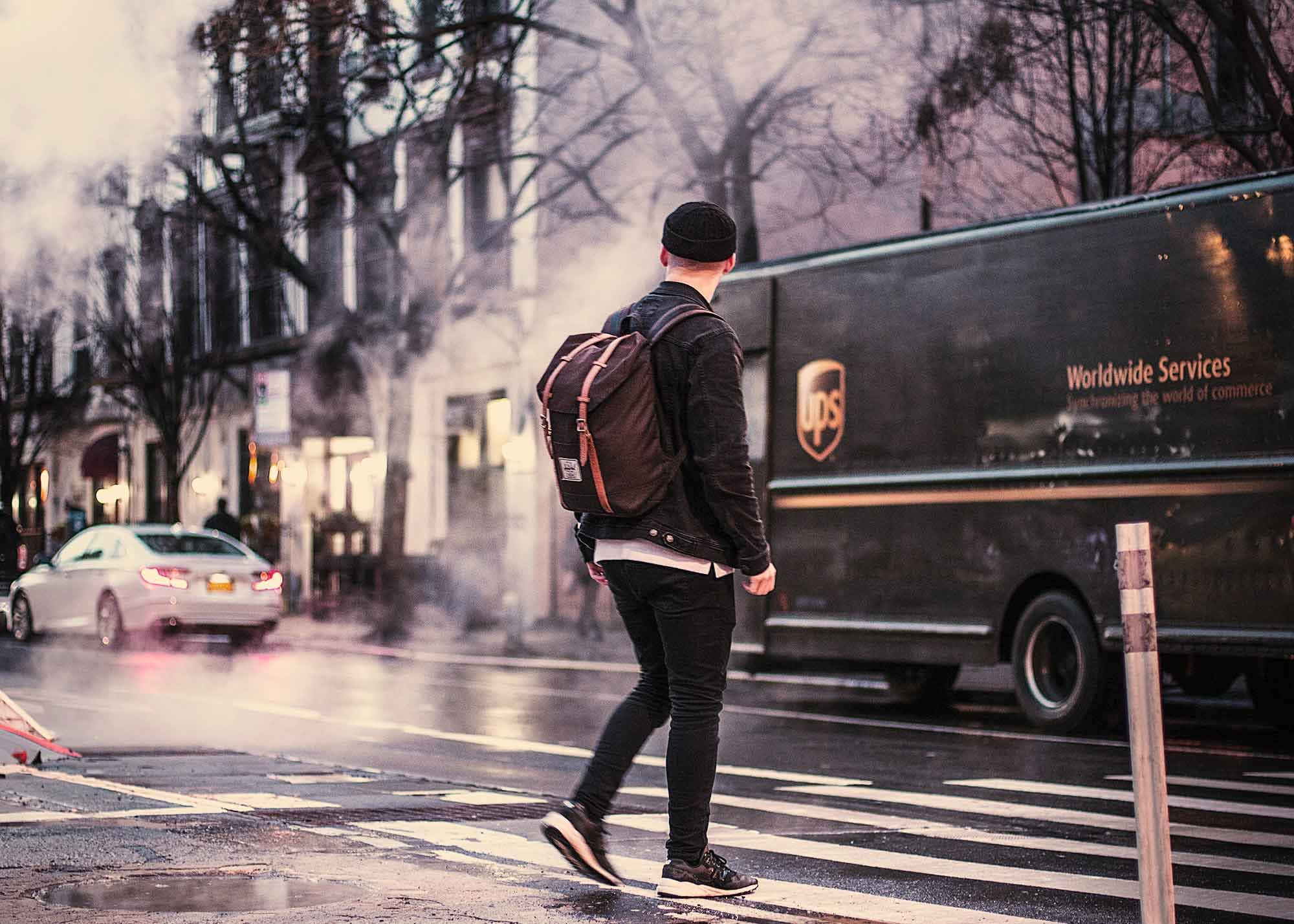 Man walking into the road with a UPS truck nearby