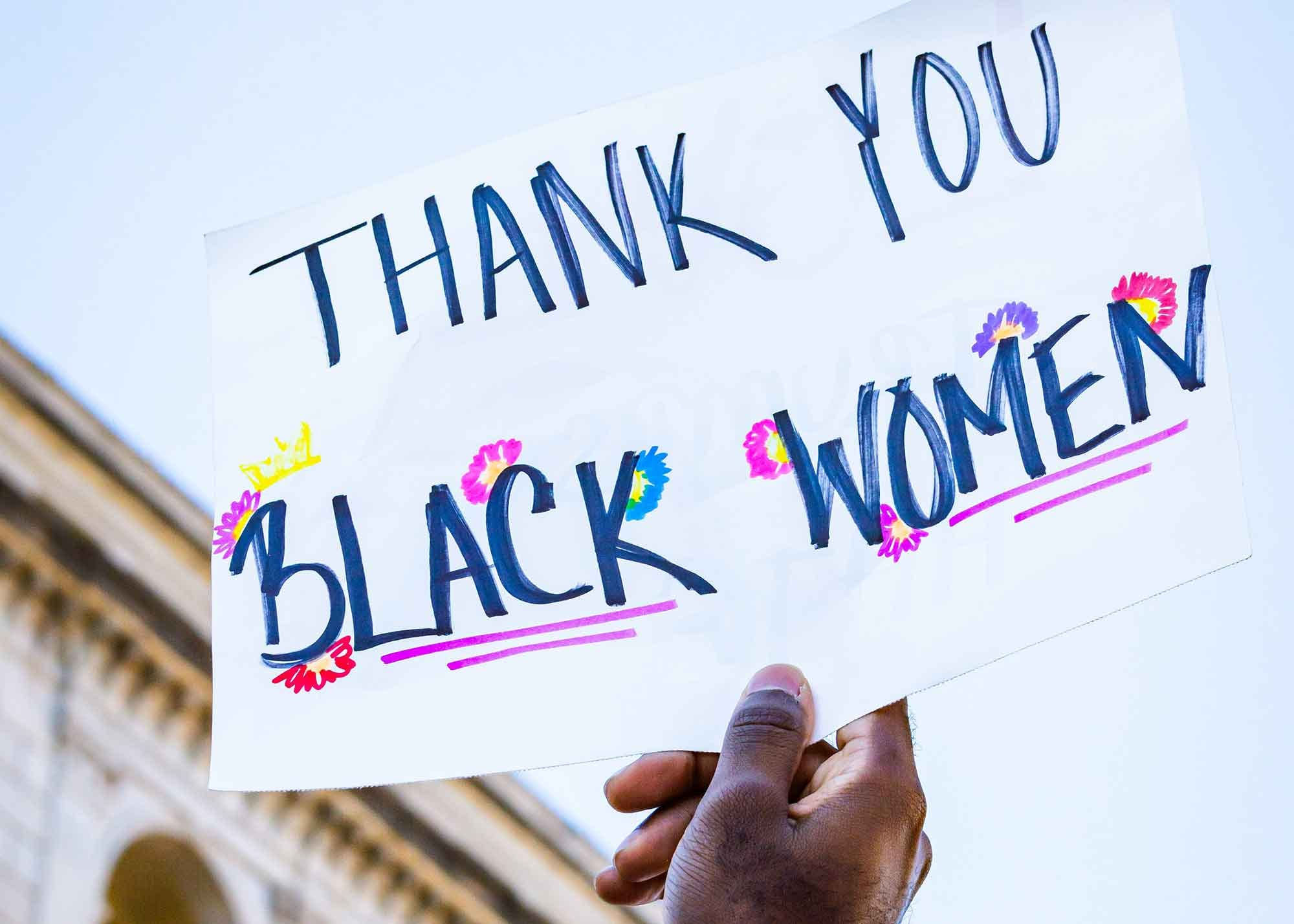 """Woman holding a sign at a protest that reads """"Thank you Black Women"""""""