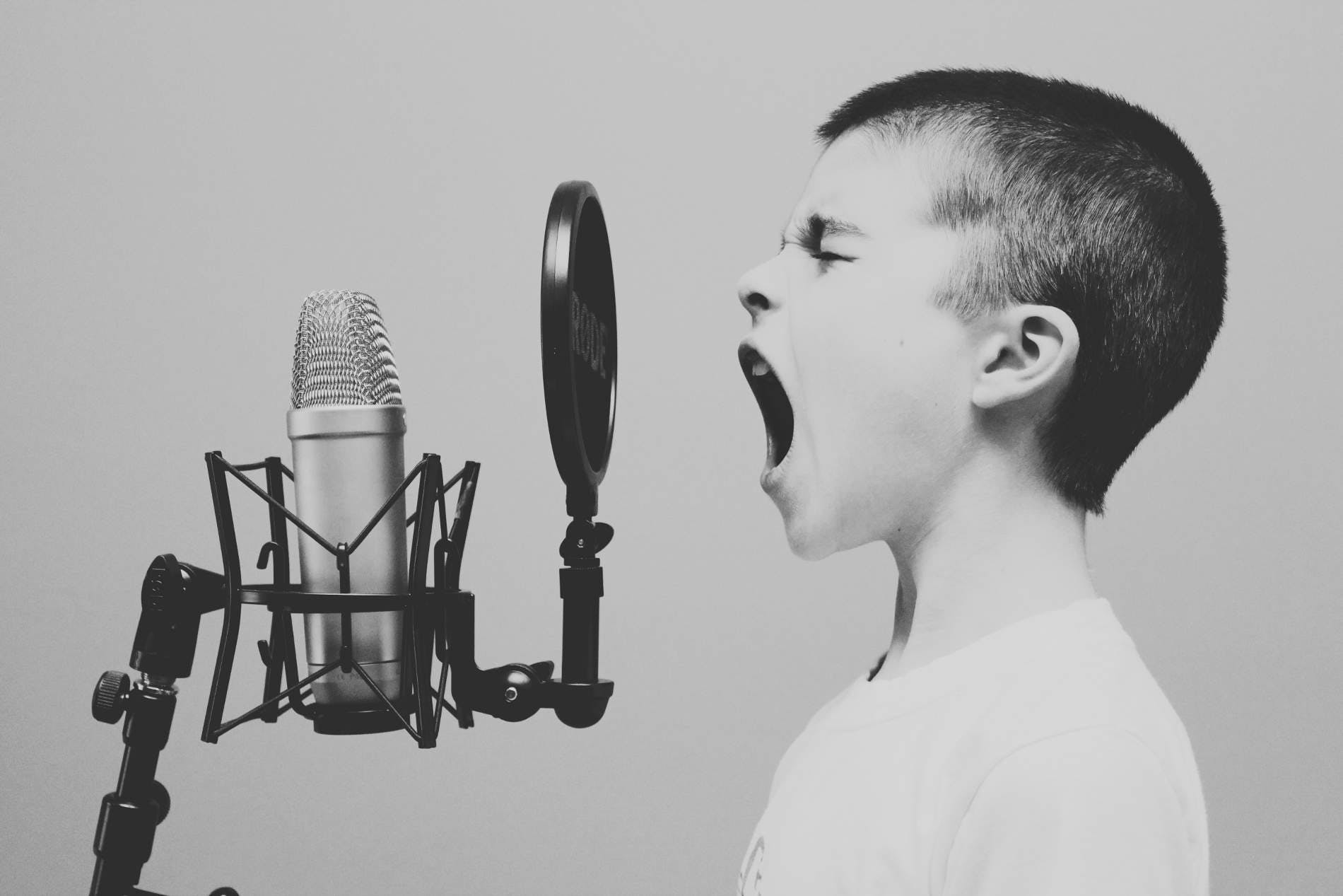 young boy singing into studio microphone