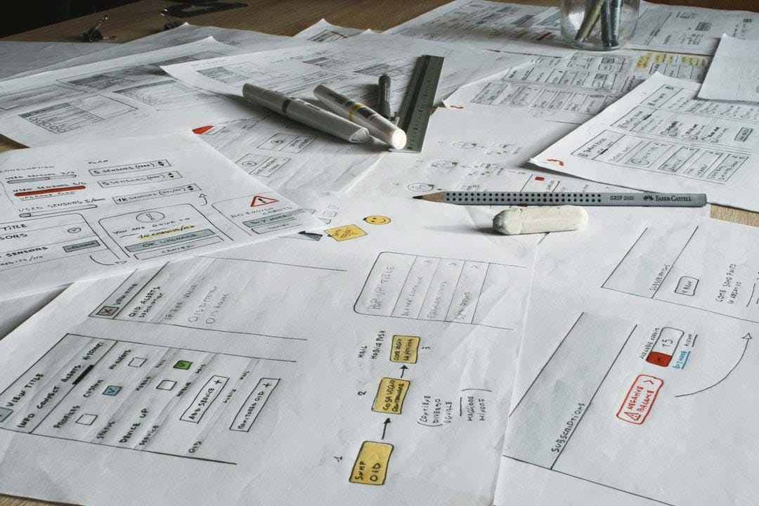 papers of wireframes laid out on table