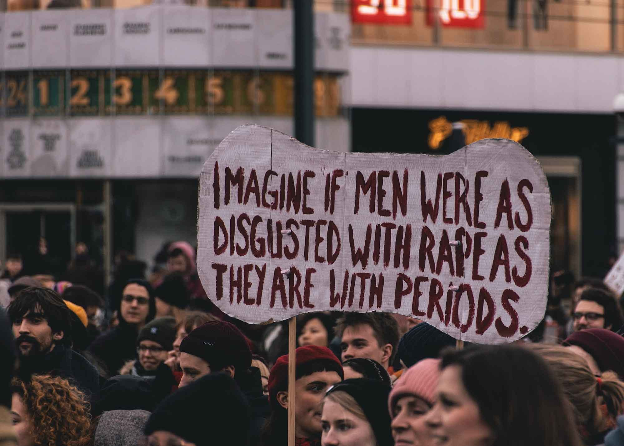 A woman holding a sign at a protest about rape