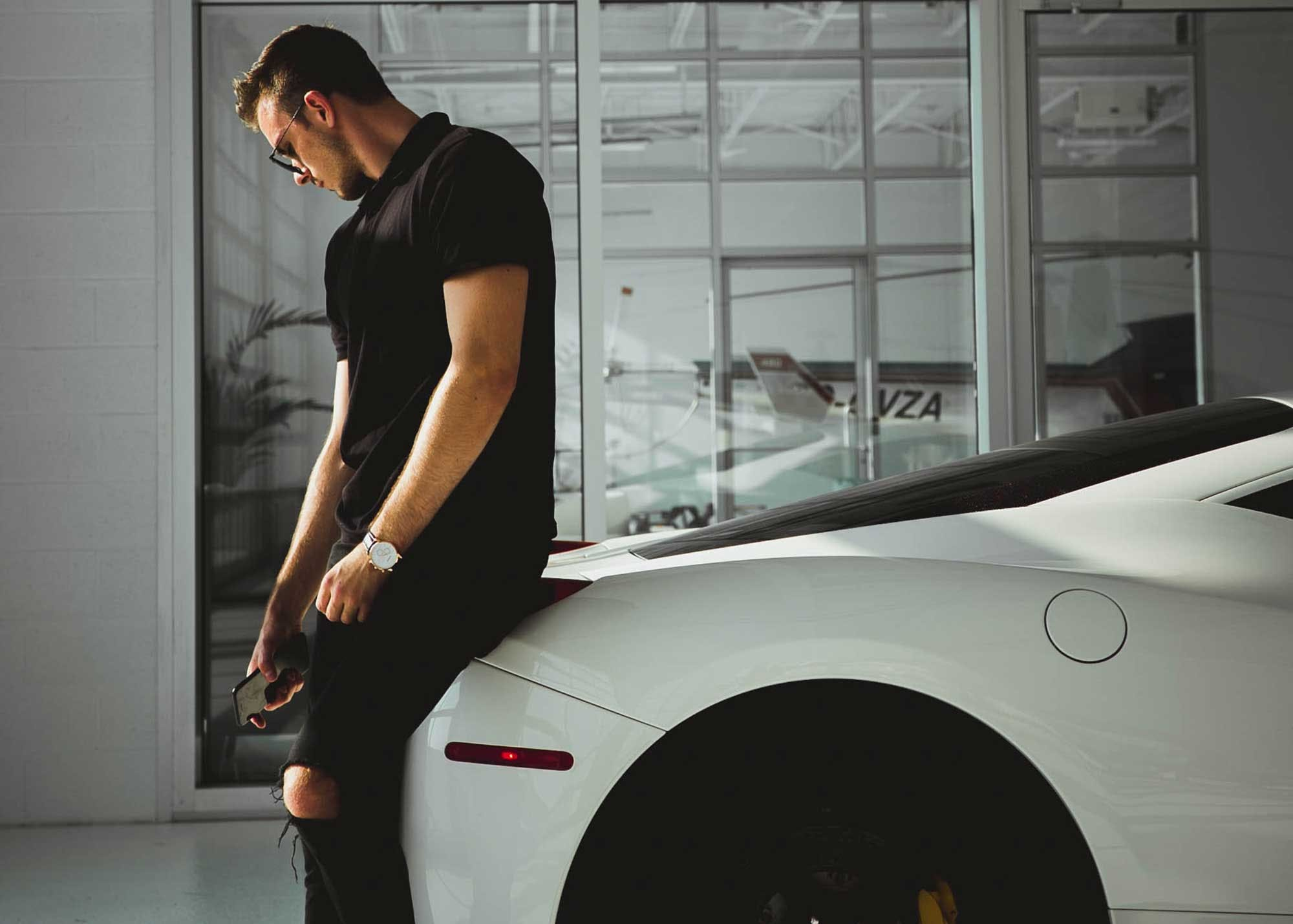 Man leaning against his luxury car