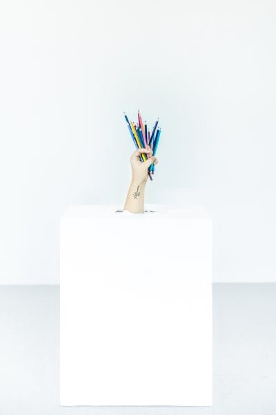 hand coming out of box holding pencils