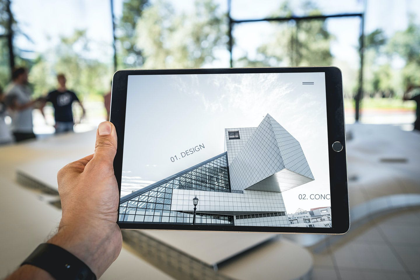 Man holding a tablet with a website for an architecture firm up