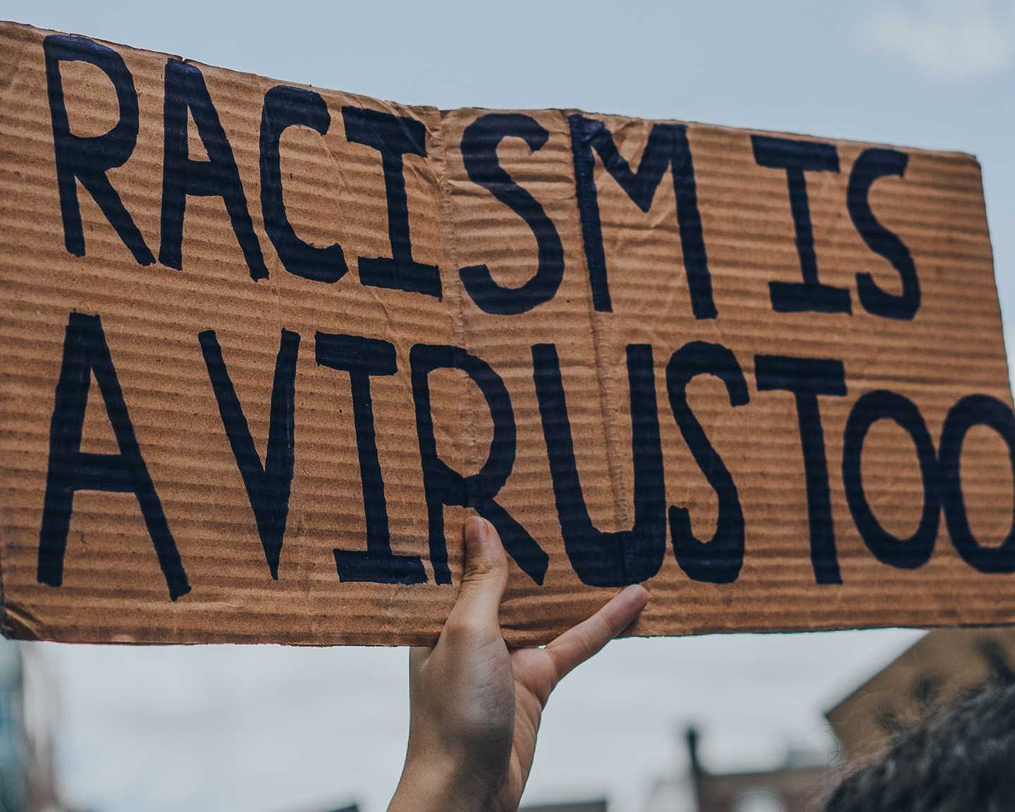 """Protester holding a sign saying """"Racism is a virus too"""""""