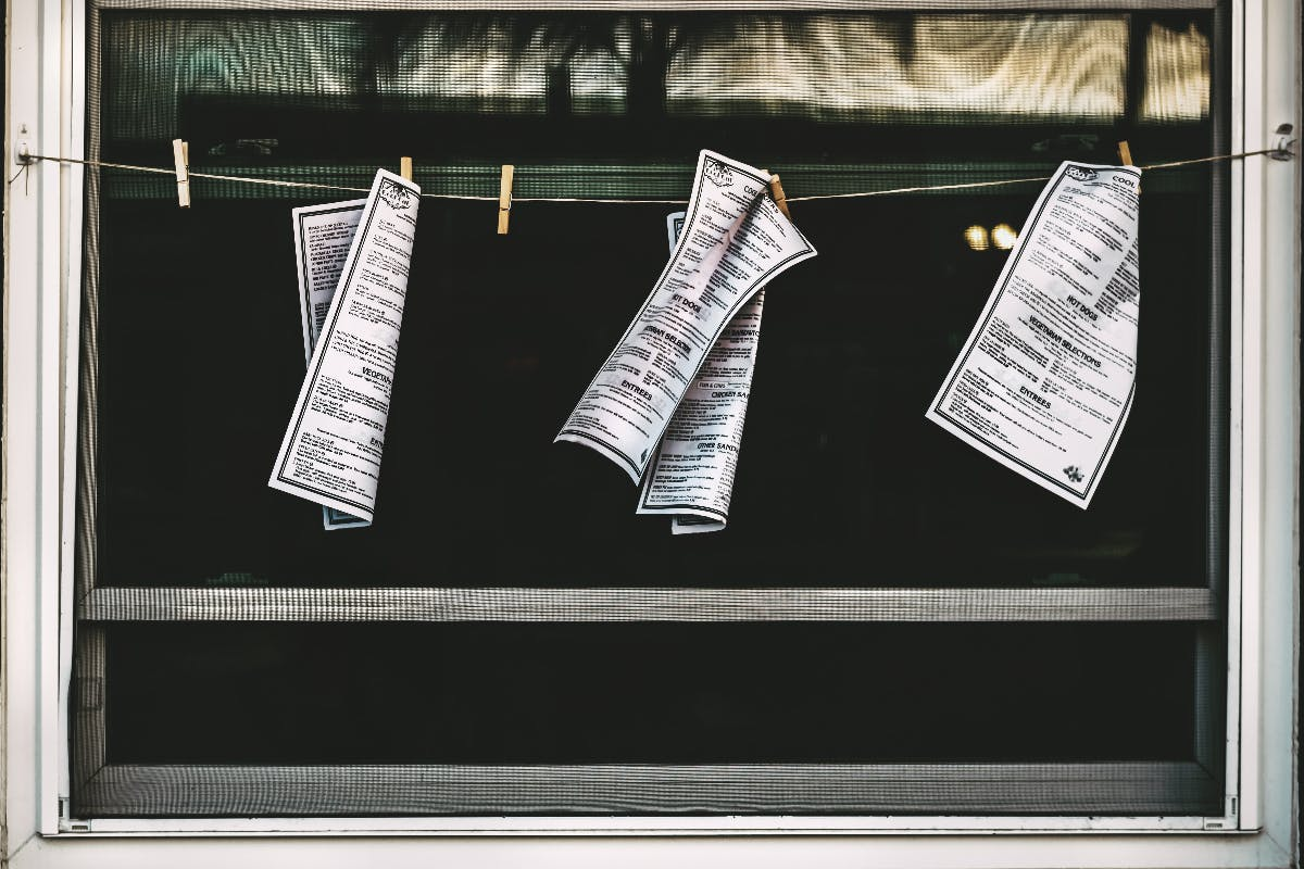 pages of a manifesto on clothespins hanging in an open window