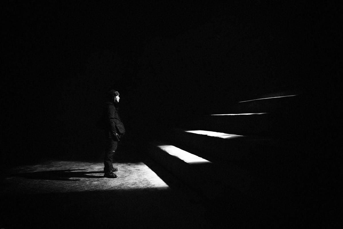 man at the bottom of dark staircasee