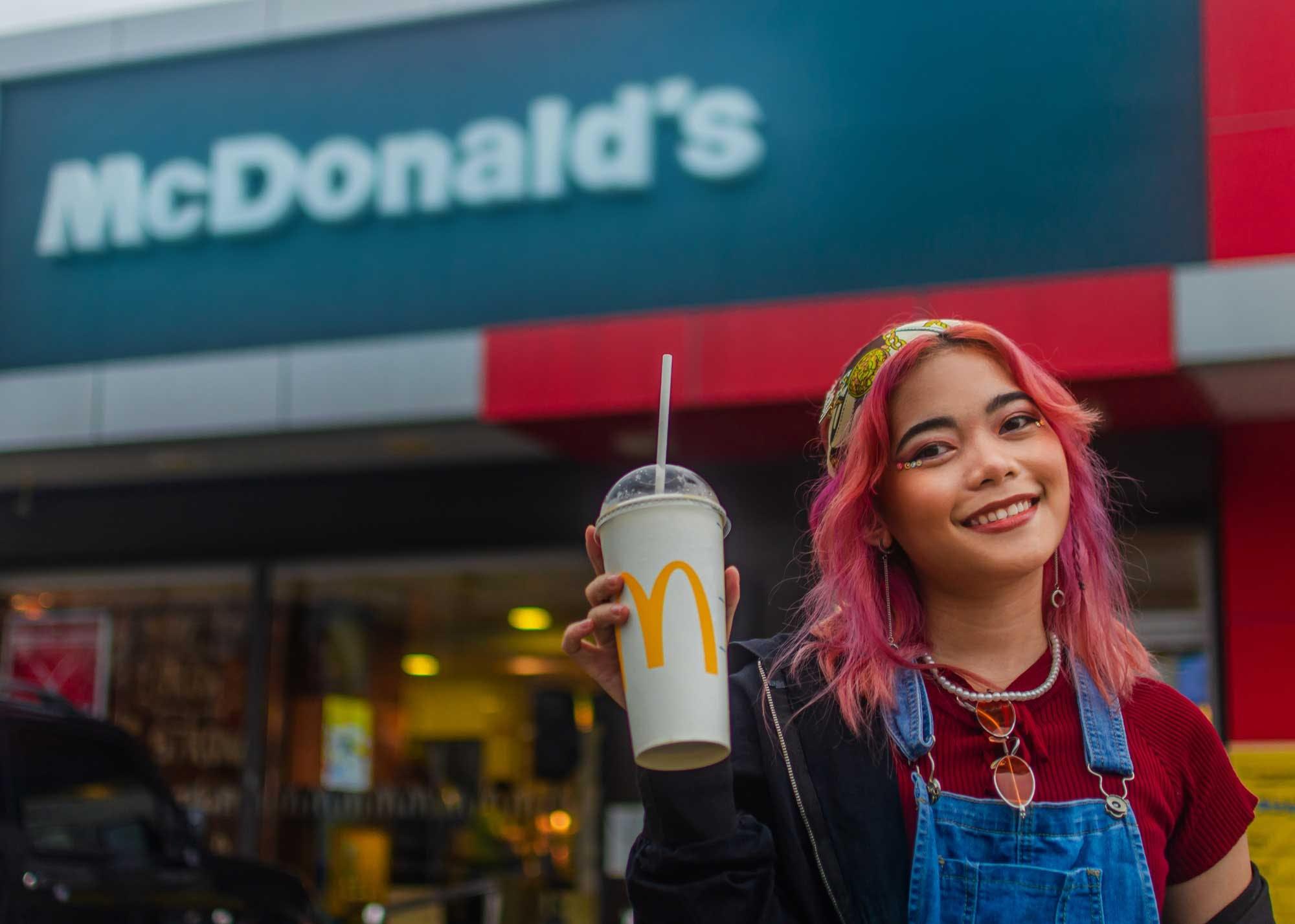 Girl enjoying a drink outside of a McDonald's