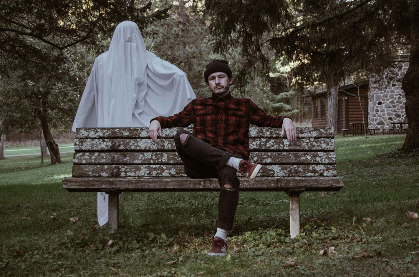 hipster man sitting on a bench in a red plaid shirt with a sheet ghost lingering behind him