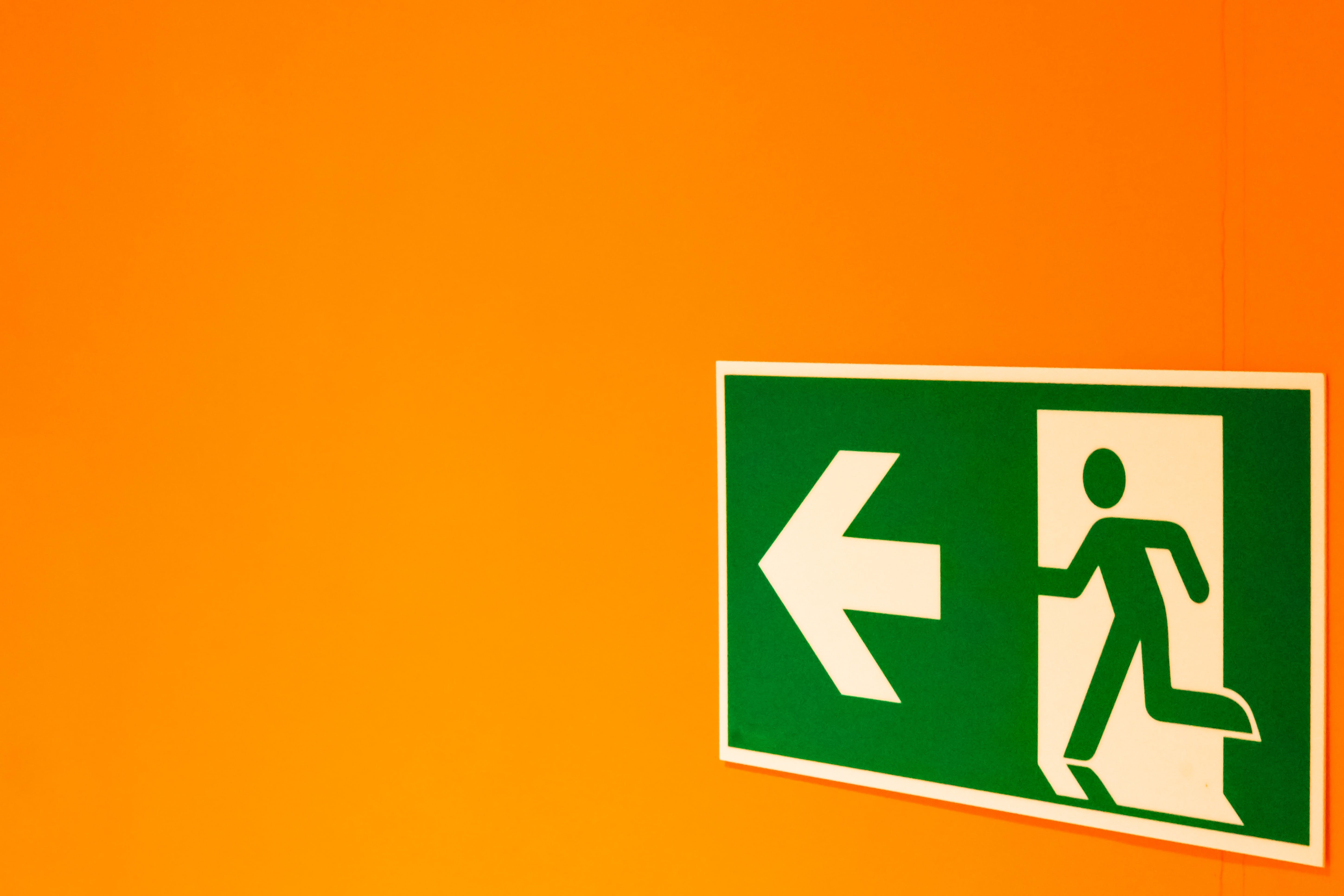 green exit sign on orange wall