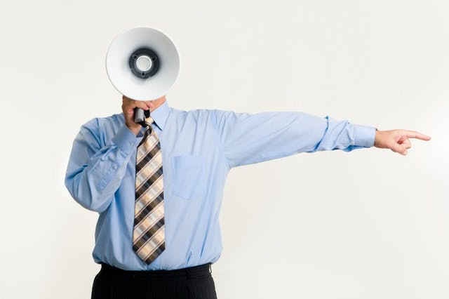 man in suit and tie with a megaphone