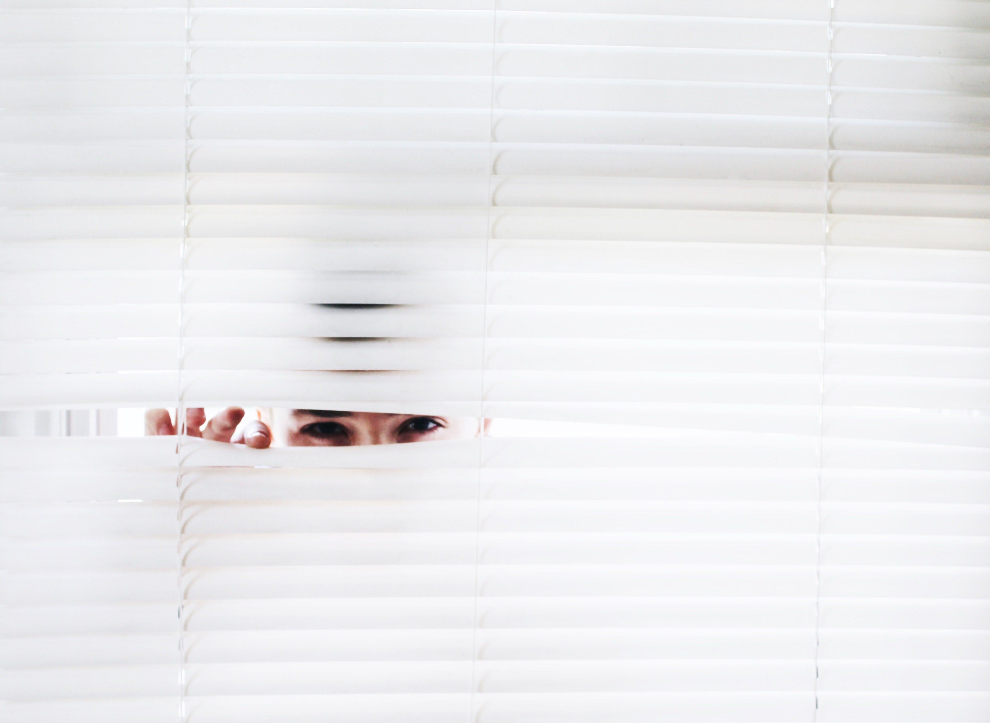 woman peeking out of blinds