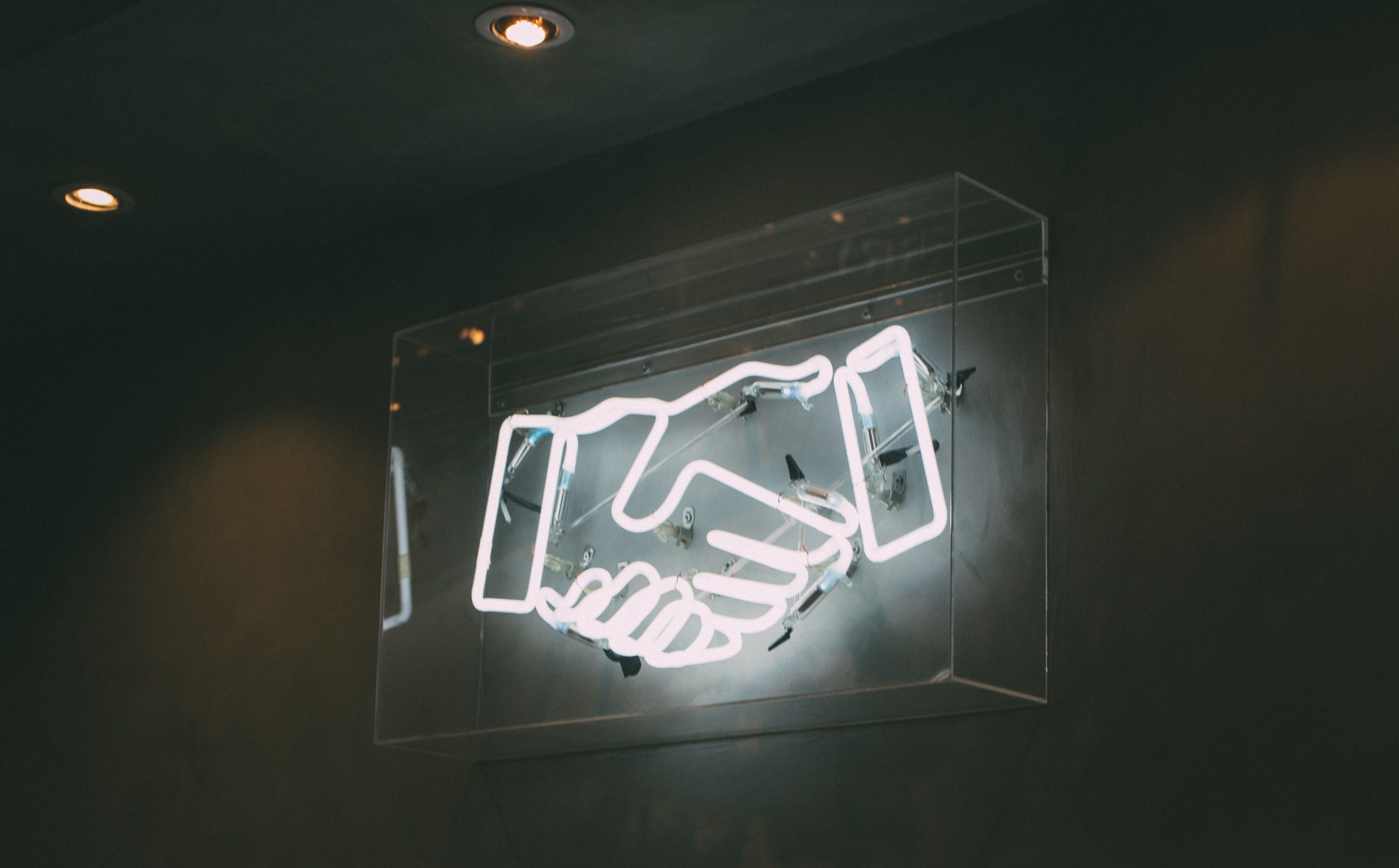 neon sign of shaking hands