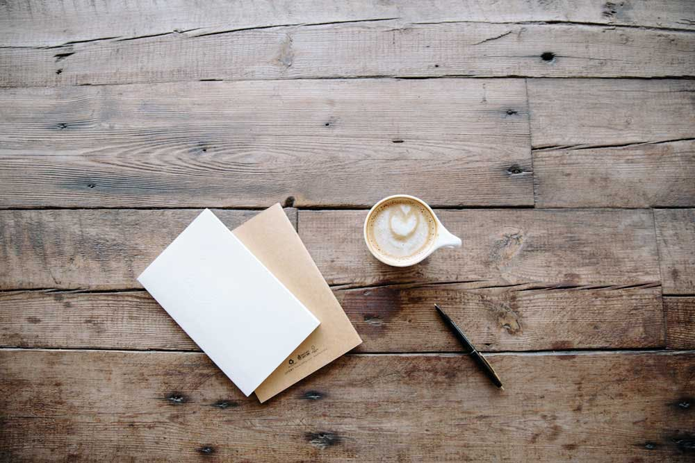 an envelope, letter and cup of coffee shot from above