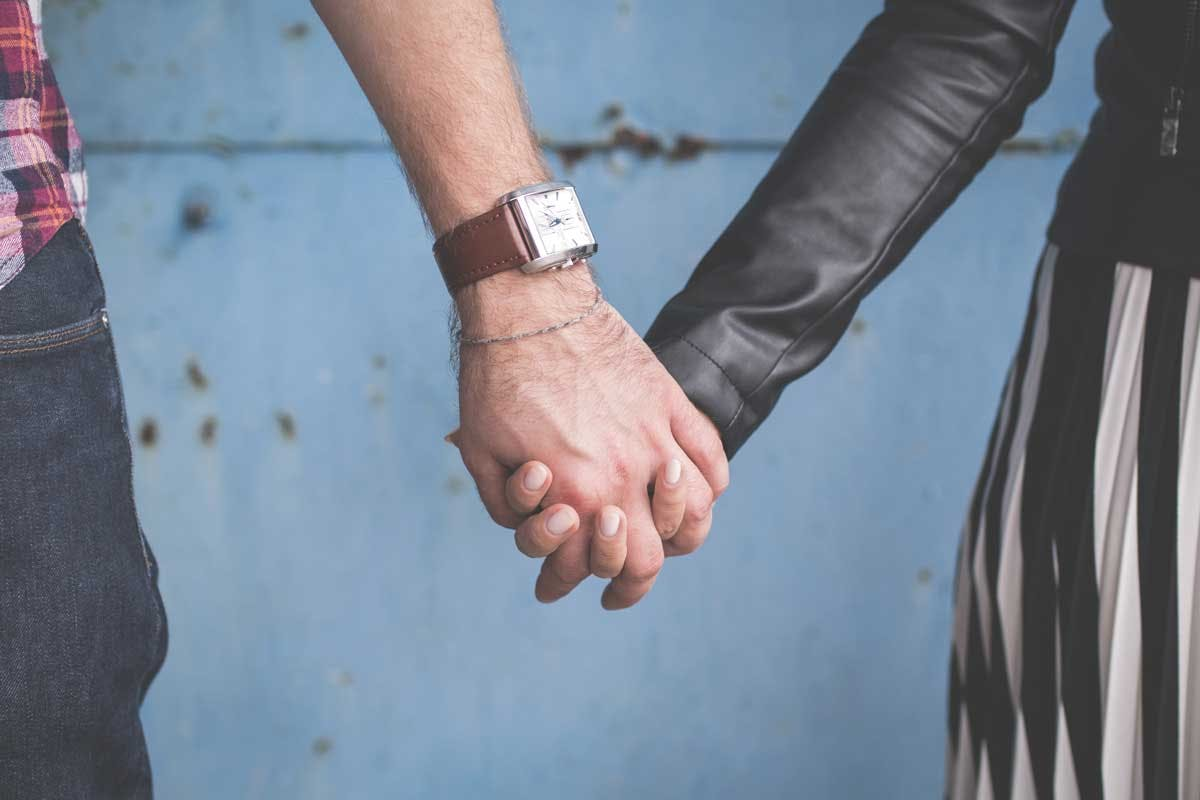 close up of man and women holding hands