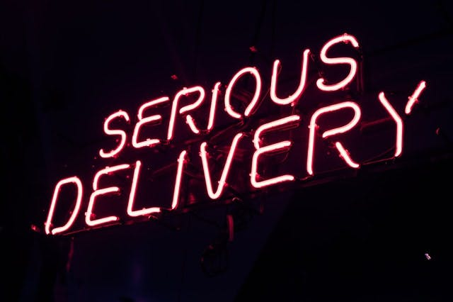 neon sign reading serious delivery