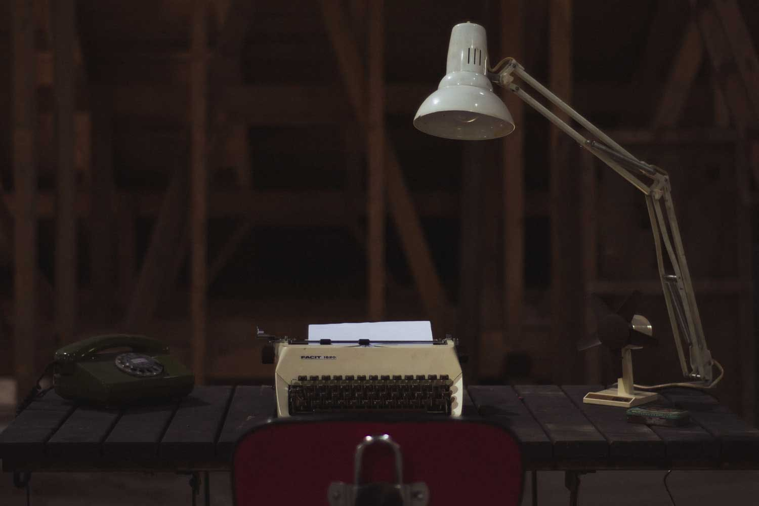A desk appointed with a typewriter and lamp