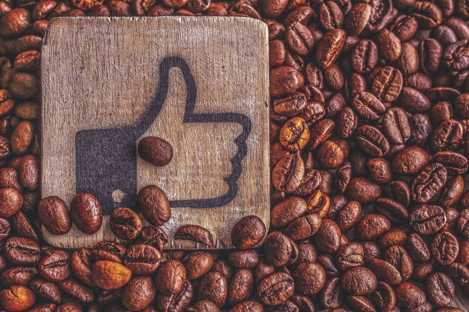 coffee beans with a wooden sign branded with the Facebook like emoticon