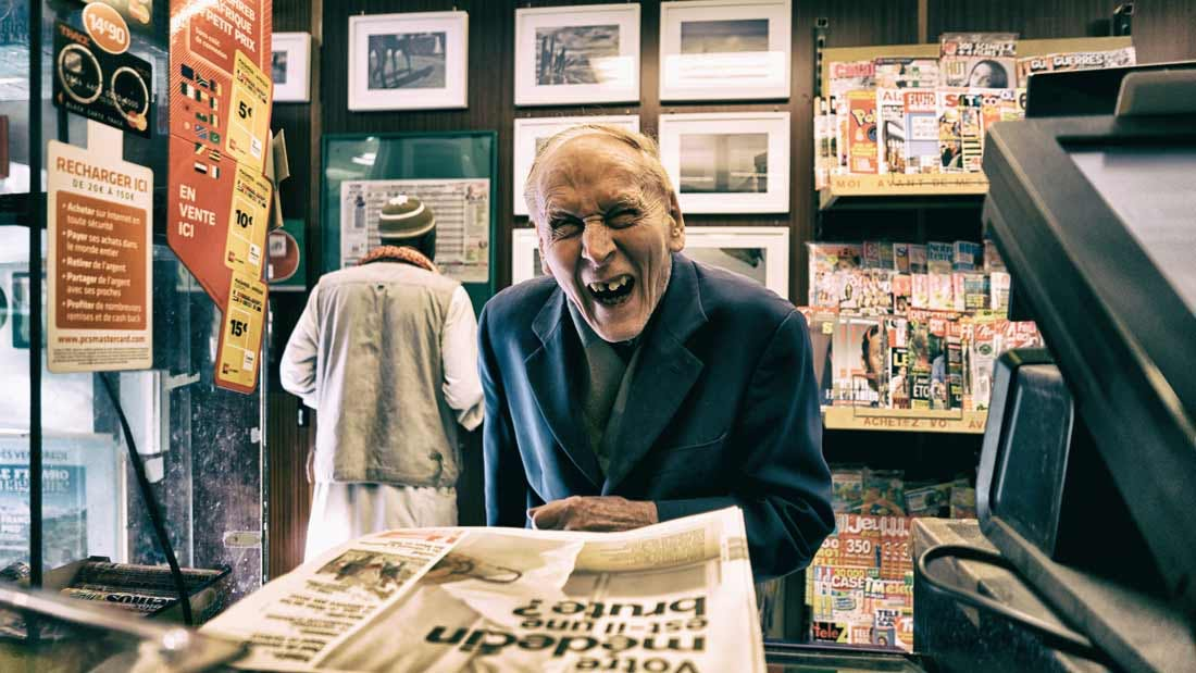 old man laughing at news stand