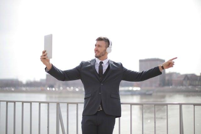 man in suit having zoom meeting on ipad