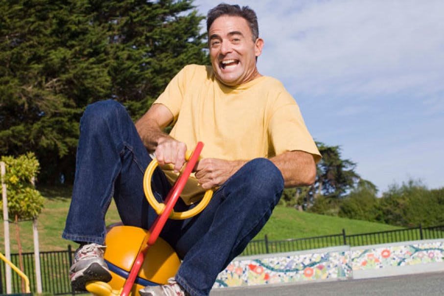 middle aged man playing at playground