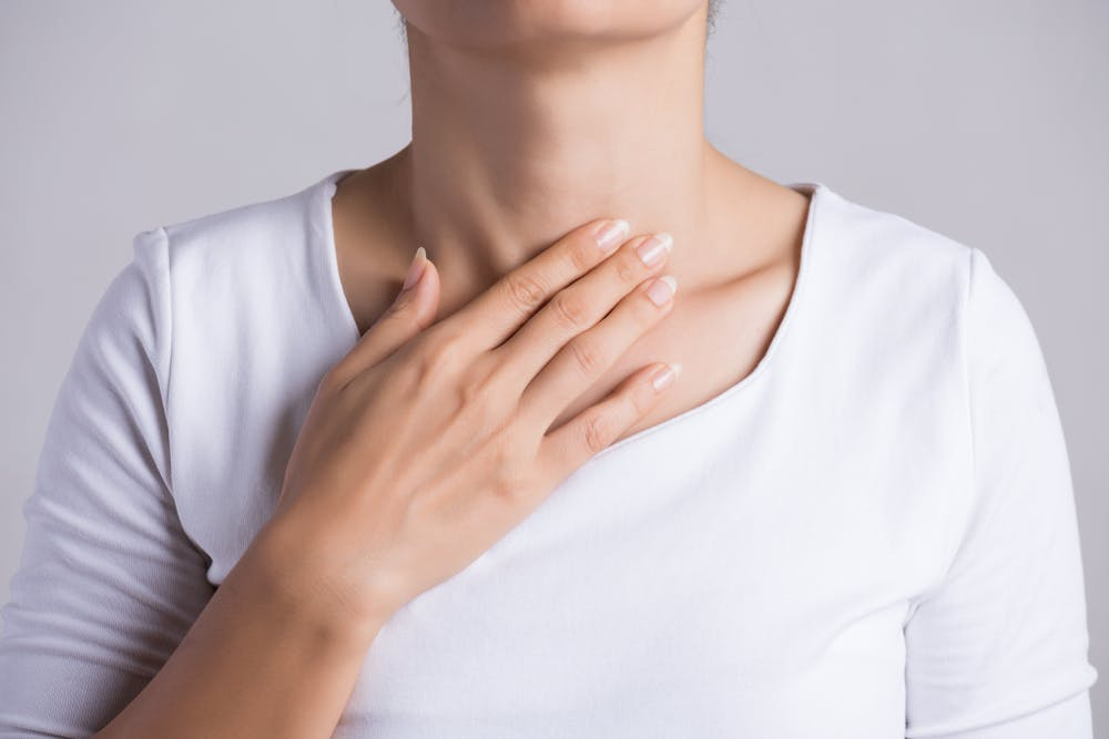 Woman touching her thyroid gland with right hand
