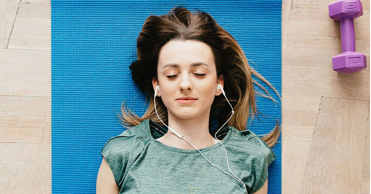 Woman lying on the floor with eyes shut listening to music