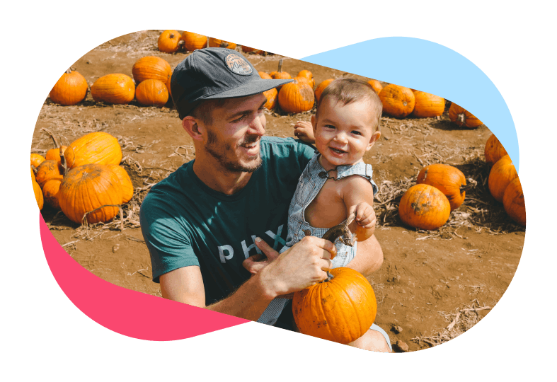 Smiling father holding son in pumpkin field