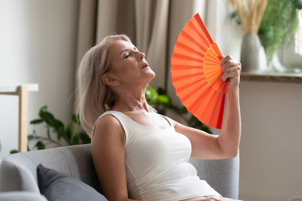 Older woman using a fan to cool herself down from a hot flush
